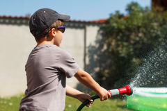 Little boy watering with hose Stock Photos