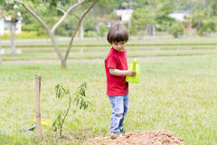 Little boy watering plants Outdoors Royalty Free Stock Image