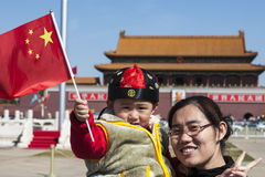 Little Boy waves chinese Flag in Forbidden City, B. Little boy on mums arm waves a chinese flag on the Tiananmen Square in front of the entrance to the Forbidden royalty free stock image