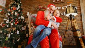 Little boy waves hand and takes pictures with Santa.