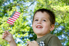 Little boy waving an American flag. Portrait of a cute brown-haired, brown-eyed boy waving an American flag as he watches a parade stock photo