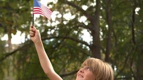 Little boy waving american flag stock footage