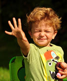Little boy waving into the sun Stock Images