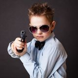 A little boy with a weapon. On a black background Stock Photo