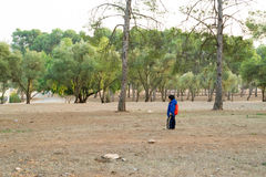 Little boy wearing a backpack all alone in the forest. Kid wearing school backpack all alone in the forest Royalty Free Stock Photo