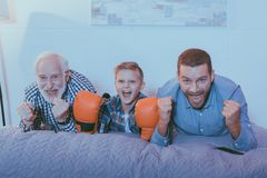 Little boy wearing boxing gloves, his father and grandfather lying on the bed, watching a boxing match royalty free stock image
