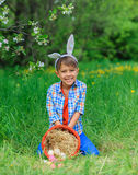 Little boy wearing bunny ears. Cute little boy wearing bunny ears playing with Easter eggs in blossoming apple garden on spring day Royalty Free Stock Photos