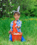 Little boy wearing bunny ears. Cute little boy wearing bunny ears playing with Easter eggs in blossoming apple garden on spring day Stock Images