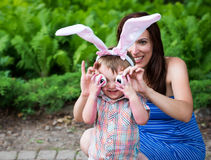Little Boy Wearing Bunny Ears and Silly Egg Eyes - Close Up. A funny portrait of a little boy having fun on Easter wearing bunny ears.  His mother helps him hold Royalty Free Stock Images