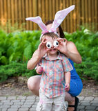 Little Boy Wearing Bunny Ears and Silly Egg Eyes. A funny portrait of a little boy smiling having fun on Easter wearing bunny ears.  His mother holds up silly Royalty Free Stock Photo