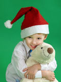 Little boy wearing a christmas hat and holding  toy, green background Royalty Free Stock Photos