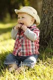 Little boy wearing a cowboy hat playing on nature Stock Image