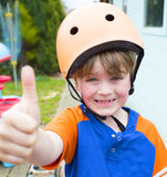Little boy wearing a cycling helmet giving thumbs up Stock Image