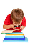 Little boy wearing glasses reading a book with a magnifying glas Stock Photo