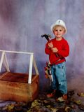 Little Boy Wearing Hard Hat. Preschool little blonde blue-eyed boy in red shirt and blue jeans is wearing a tool belt and wielding a large hammer Stock Photos