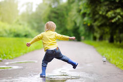 Little boy wearing rain boots jumping in pool of water Royalty Free Stock Photography