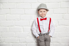 Little boy wearing a red bow tie, suspenders and white shirtand against a white brick wall Royalty Free Stock Image