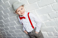 Little boy wearing a red bow tie, suspenders and white shirtand against a white brick wall Royalty Free Stock Photography
