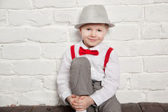 Little boy wearing a red bow tie, suspenders and white shirtand against a white brick wall Royalty Free Stock Photo