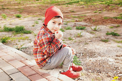 A little boy wearing a red hat, a jacket, and sneakers is sitting in the park. sunny day Royalty Free Stock Photos