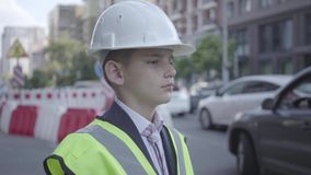 Portrait cute little boy wearing business suit and safety equipment and constructor helmet standing on a busy road in a stock footage