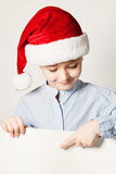 Little Boy Wearing Santa Hat Point the Finger at White Paper Stock Photography