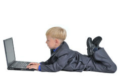 Little boy wearing suit working on laptop Royalty Free Stock Image