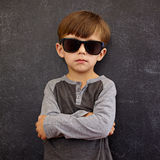 Little boy wearing sunglasses posing with his arms crossed Stock Photos