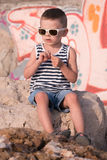 Little boy wearing sunglasses and shirt sitting in front of wall with graffiti Royalty Free Stock Images