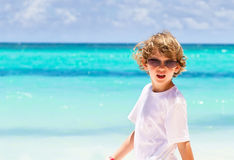 Little boy wearing sunglasses on tropical beach Stock Images