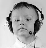 Little boy wearing telephone headset. Serious little boy in ear-phones with a microphone in call center answers a call on a white background Royalty Free Stock Photography