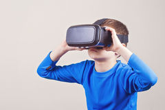 Little boy wearing virtual reality goggles watching movies or playing video games. Little kid wearing virtual reality VR goggles watching movies or playing video Stock Photography
