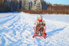 Little boy wearing warm jumpsuit stands with sled Royalty Free Stock Photography