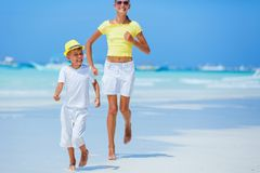 Boy with his sister having fun on tropical ocean beach. Kid during family sea vacation. Royalty Free Stock Images