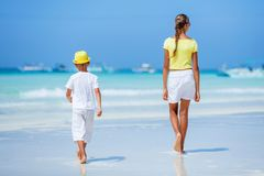 Boy with his sister walking on tropical ocean beach. Kid during family sea vacation. Royalty Free Stock Photos