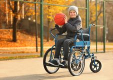 Little boy in wheelchair with ball. On playground royalty free stock photo