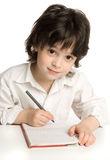 The little  boy which drawing. The little boy which drawing of pencil in notebook Stock Image