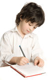 The little  boy which drawing. The little boy which drawing of pencil in notebook Royalty Free Stock Photo