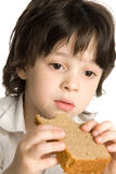The little boy which eating a bread on desk Royalty Free Stock Photos