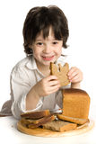 The little boy which eating a bread on desk Royalty Free Stock Photography