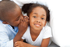 Little boy whispering something to his sister Stock Photo