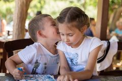 A little boy are whispering something to a pretty girl in a street restaurant. Children`s friendship Stock Image
