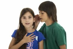 Little boy whispering something to surprised girl, isolated on w Stock Photos