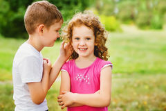 The little boy whispers a secret on an ear. The little boy whispers a secret on an ear to the girl royalty free stock photo