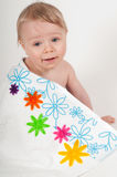 Little boy in white blanket with flowers Royalty Free Stock Images
