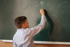 Little boy white down something on blackboard. Clever male royalty free stock photo