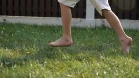 Little boy with dirty bare feet runs fast on green grass. Little boy in white shorts with dirty bare feet runs fast on green grass on sunny day close low angle stock footage