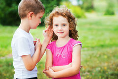 Little boy in white t-shirt whispers a girl in red dress. Stock Image