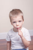 Little boy in white tshirt sucking lollipop in his Royalty Free Stock Images