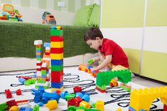 The little boy who build towers with plastic cubes Stock Image